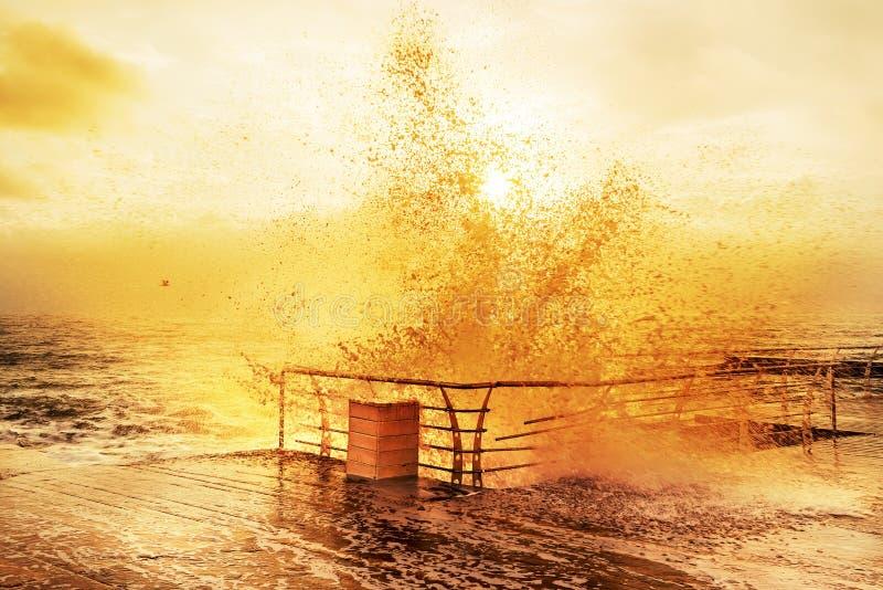 Solig realitet mycket av energimorgonen på havet Vågor med färgstänk som kraschar på en träbrygga royaltyfri bild
