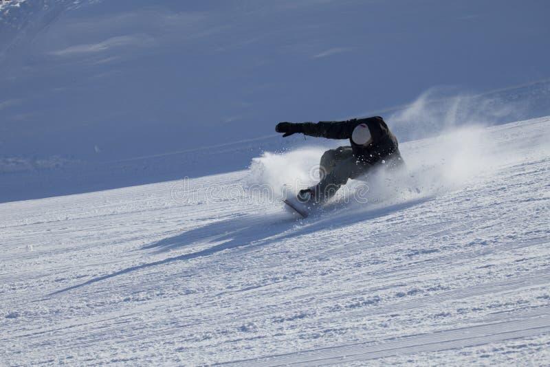 solig sluttande snowboarder för dag arkivbild