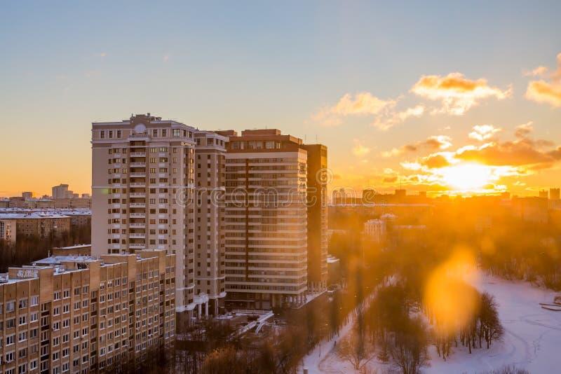 Solig solnedgång över staden övervintrar trees för snow för sky för lies för frost för mörk dag för bluefilialer Olika arkitekton arkivbilder