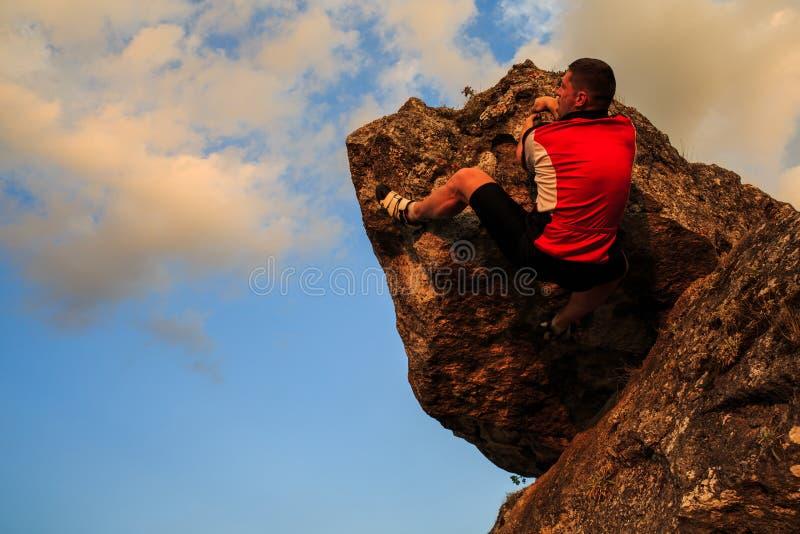 solig sommar för rock för klättringdagman Barnet passade, den starka manliga klättraren royaltyfria bilder