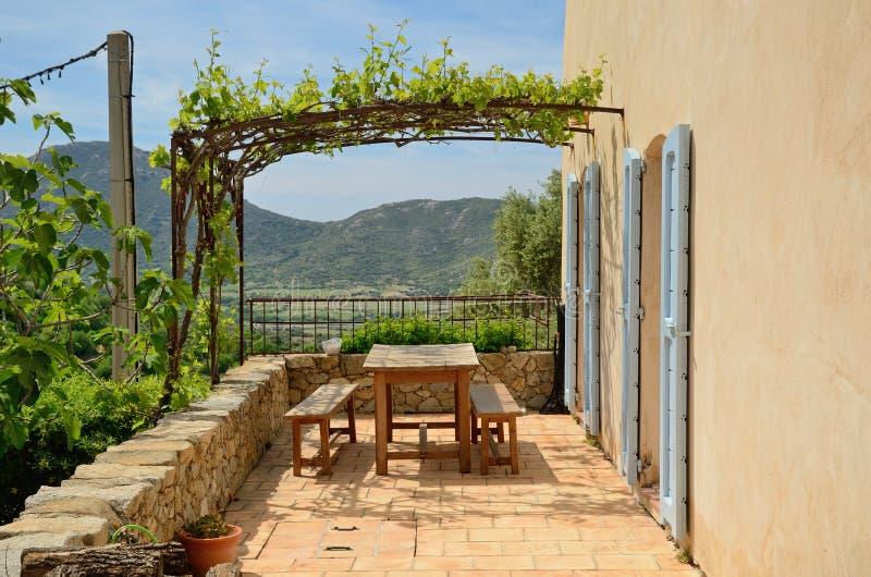 Solig terrass i den korsikanska bergstoppbyn Pigna royaltyfri bild