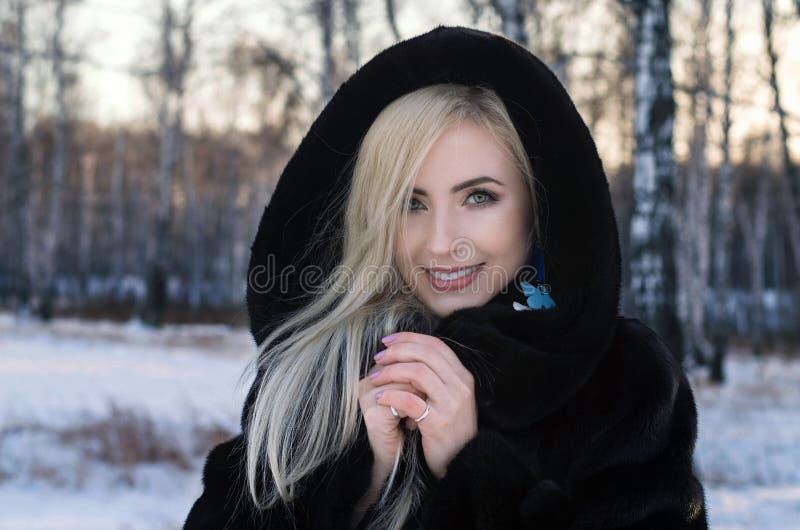 Solig utomhus- vinterst?ende av den unga attraktiva kvinnan arkivfoto