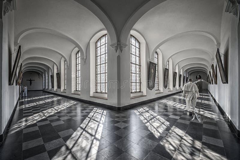 Soliga hall av en abbotskloster med skuggor av munken royaltyfria bilder