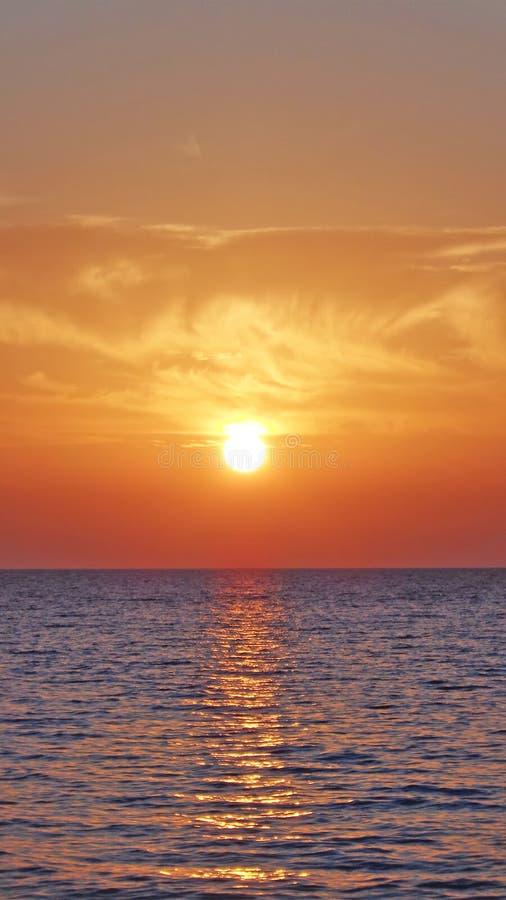 Soliga moln över havet på solnedgången arkivbilder