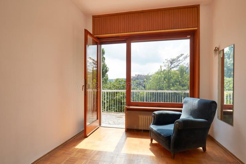 Soligt rum som är inre med terrassen och den blåa sammetfåtöljen i landshus royaltyfri fotografi