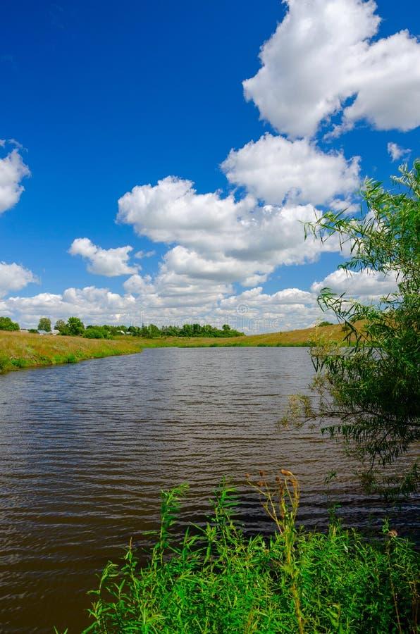 Soligt sommarlandskap med floden, lantgårdfält, gröna kullar och härliga moln i blå himmel arkivfoton