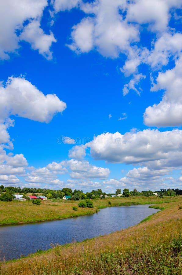Soligt sommarlandskap med floden, lantgårdfält, gröna kullar och härliga moln i blå himmel arkivbilder