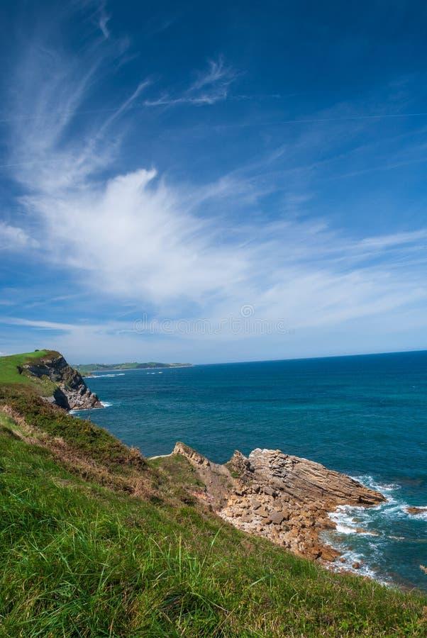 Soligt vertikalt landskap av den steniga kusten med det blåa havet arkivbilder