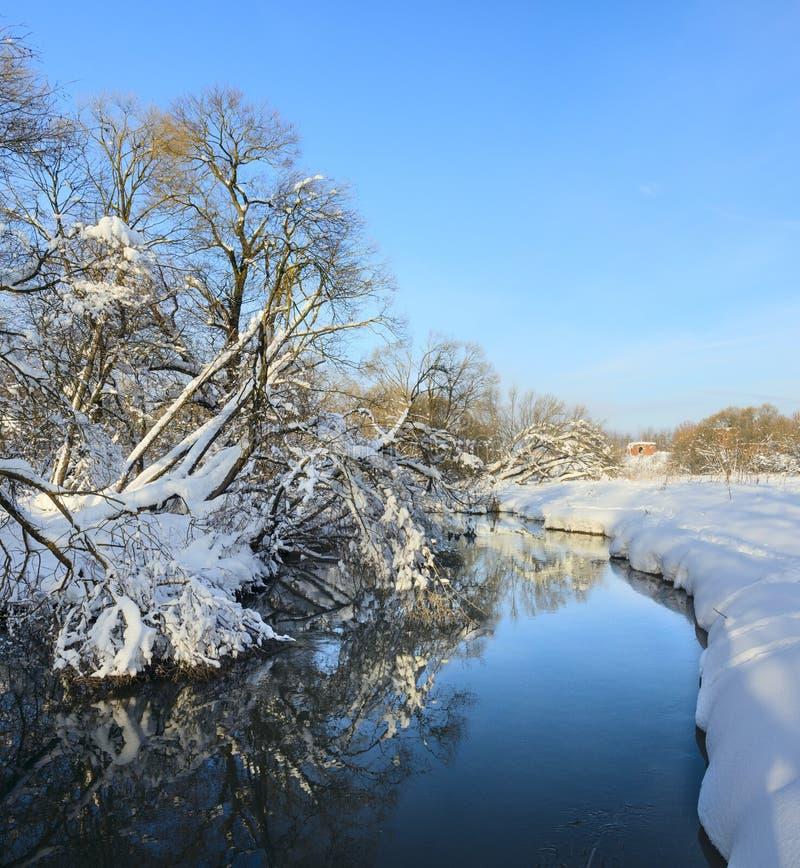 Soligt vinterlandskap med den flödande floden royaltyfri bild