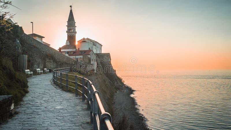 Solinställning bak klockatornet i sjösidastaden av Piran, Slovenien royaltyfri foto