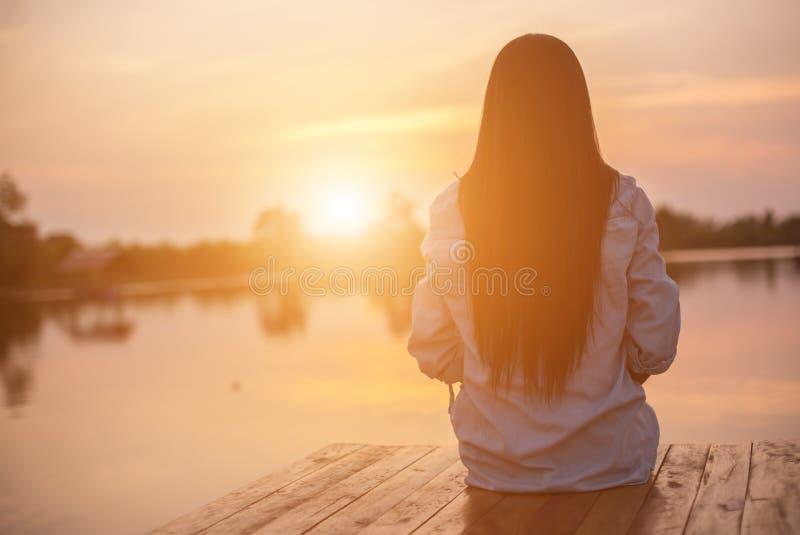 Solitária mulher triste por pôr do sol fotos de stock royalty free