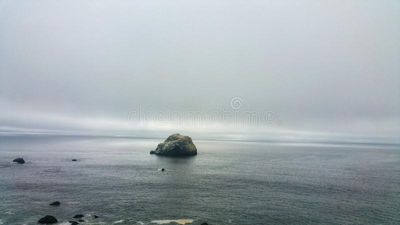 Solitaire kei tegen humeurige oceaanhemel Grimmig mistig verdwijnend punt Achtergrond minimalism stock afbeelding