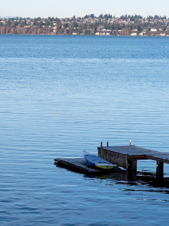 Solitaire rubberboot op houten dok, exemplaarruimte stock afbeelding
