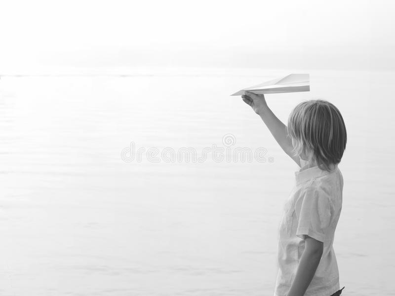 Solitary boy playing with his toy airplane Paper. Solitary boy plays with his toy airplane Paper royalty free stock images