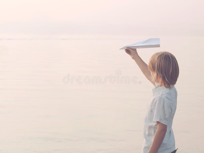 Solitary boy plays with his toy airplane Paper. Solitary boy playing with his toy airplane Paper stock photo
