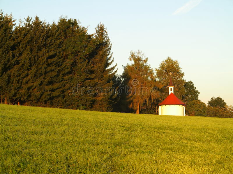Solitary chapel countryside at sunrise. A solitary chapel in a peaceful rural environment - captured at that magical moment by sunrise when the meadow glimmers stock image