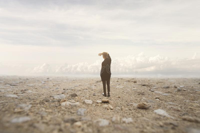 Solitary man looks at the infinite in a surreal and spectacular landscape royalty free stock photo