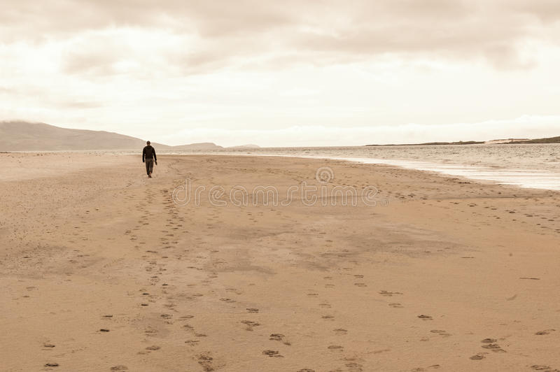 Solitary man taken from behind walking in an empty beach. stock image