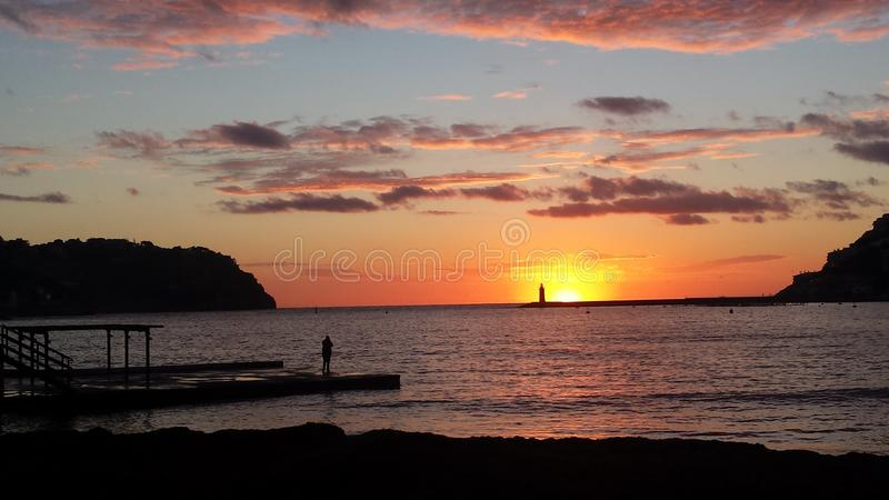 Solitary at sundown. Scene of a solitary person enjoying the moment of a beautiful colourful and memorable sunset stock image