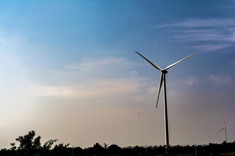 Solitary Wind Turbine on blue sky background stock images