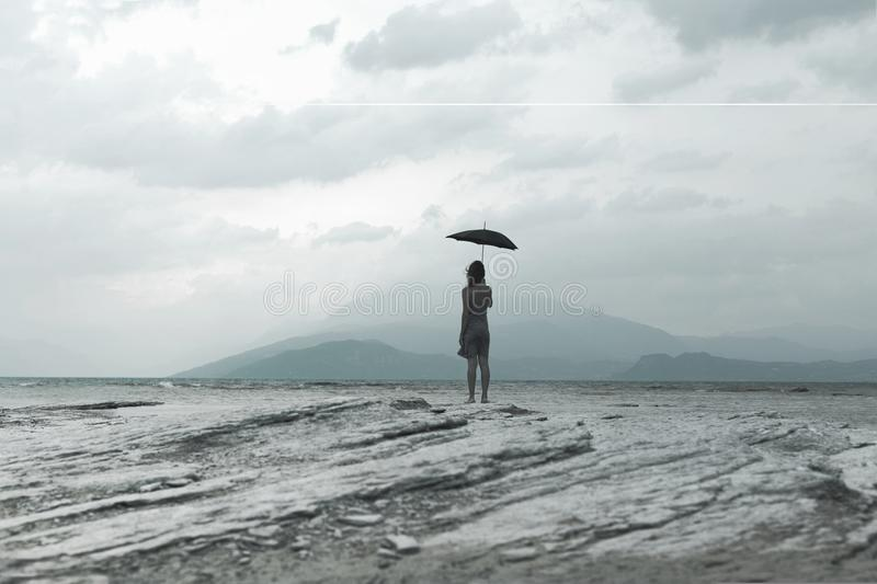 Solitary woman looks at infinity and uncontaminated nature on a stormy day. Lonely woman looking at infinity and uncontaminated nature on a stormy day royalty free stock photo