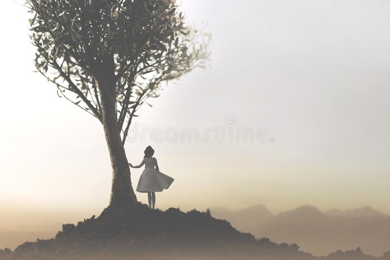 Solitary woman under a tree looking at a mystical and suggestive landscape stock photography