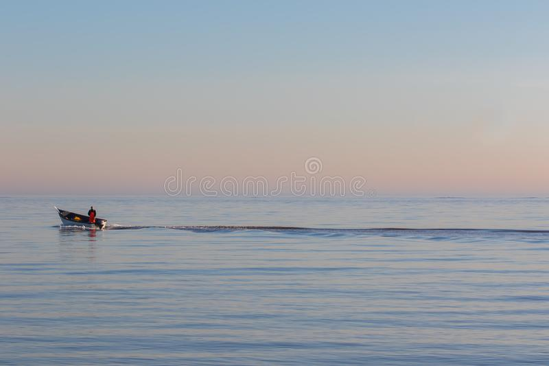 Solitude. Alone at sea. Small fishing boat on the ocean royalty free stock photo