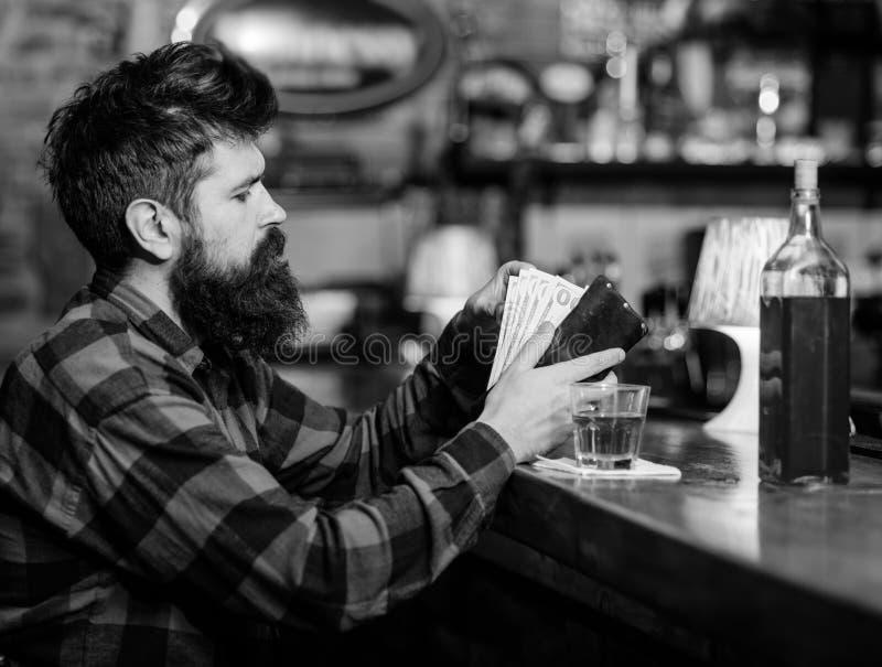 Solitude d'alcoolisme Le hippie tient le portefeuille, comptant l'argent pour acheter des boissons photo libre de droits