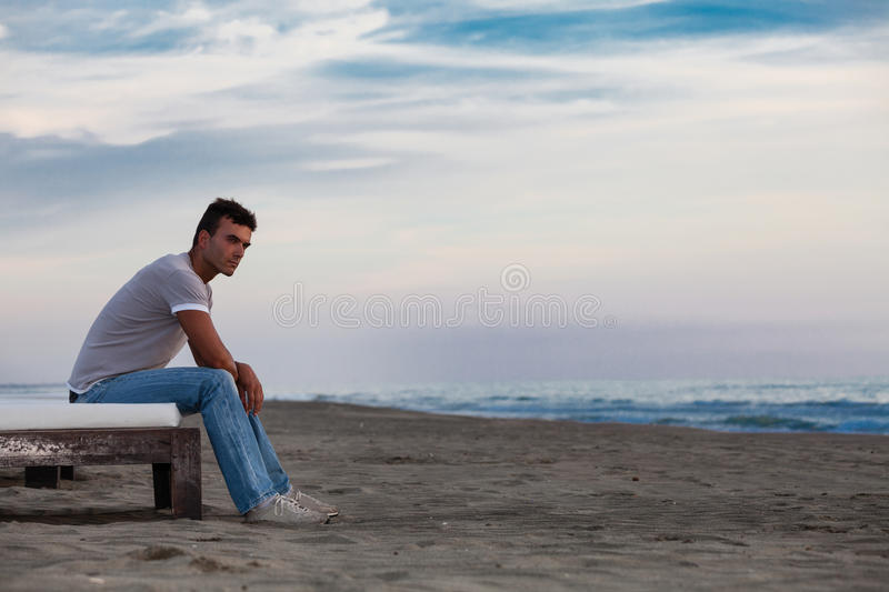Solitude. Lonely man on the beach to the sea. stock image