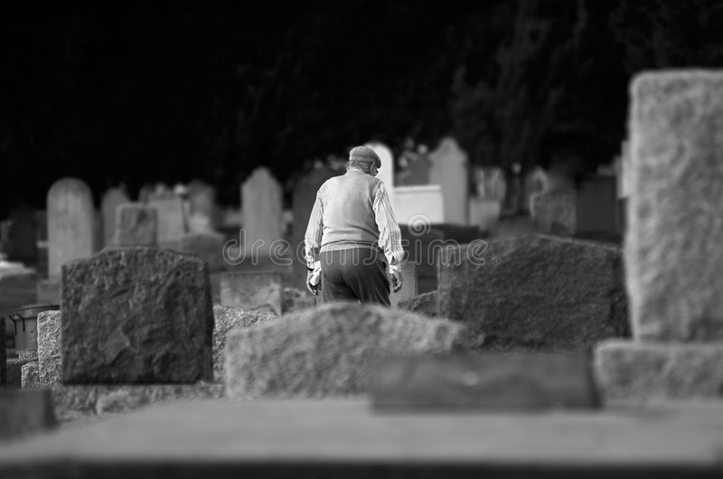 Solitude and Sadness. Old man walking alone through cemetery