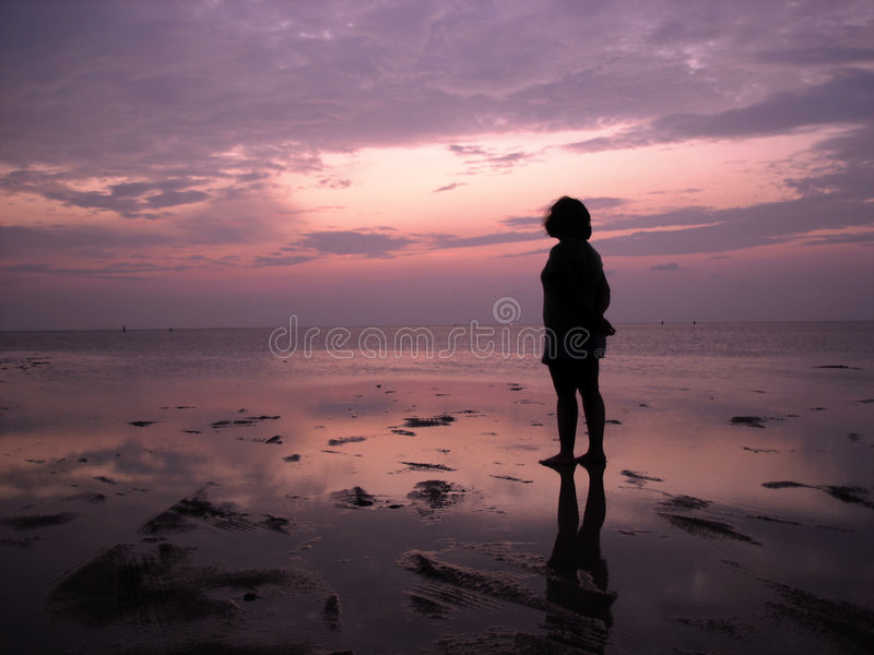 Solitude at Sunset. A young woman gazes out upon the bay as the tide slowly covers the beach stock photo