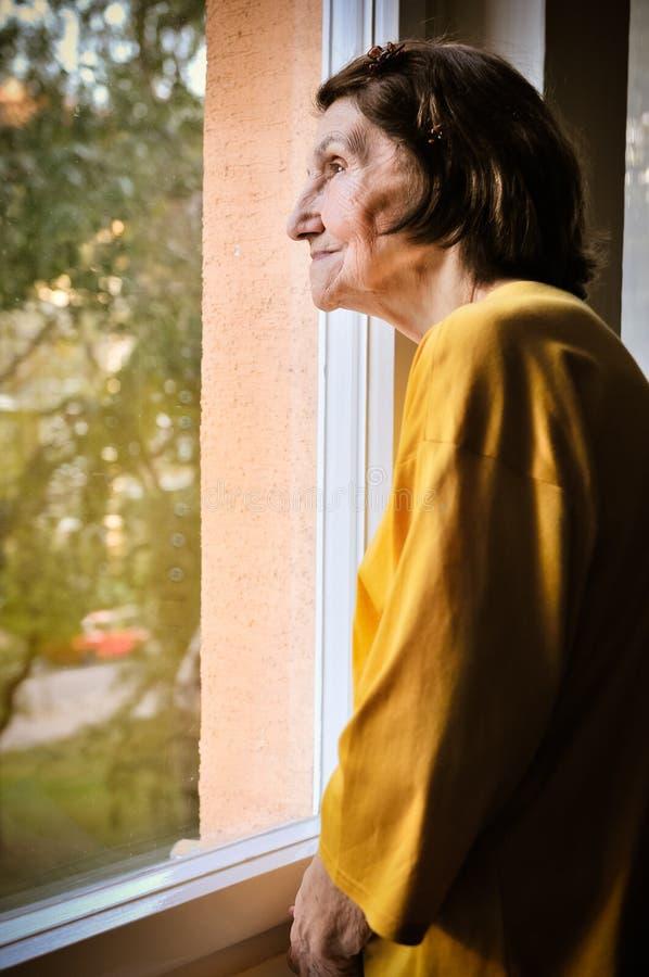 Solitudine - donna senior che guarda attraverso la finestra fotografia stock