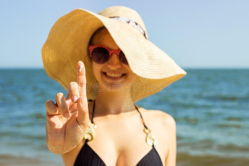 Solkrämkvinna som applicerar sol- kräm för sunscreen Härlig lycklig gullig kvinna som applicerar solbrännakräm Sunscreen på fingr arkivbild