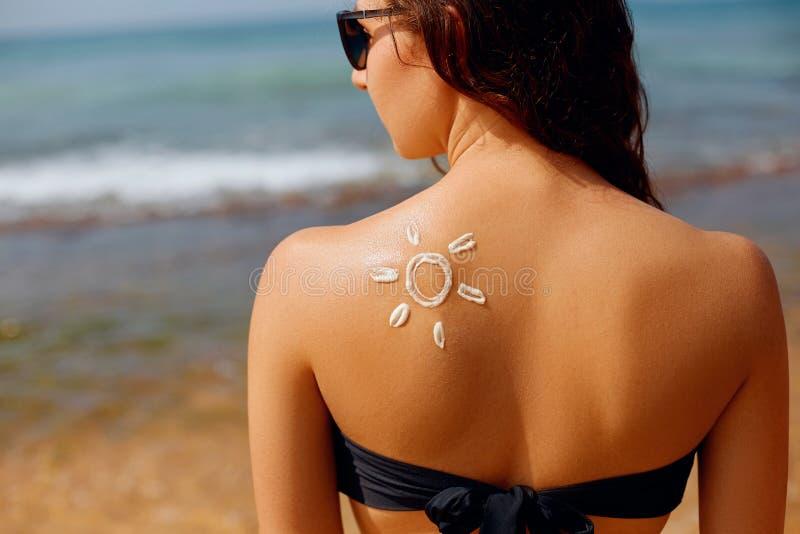 Solkr?m Härlig kvinna för solkräm som applicerar på brunbränd skuldra i formen av solen Sol- kräm för Sunscreen arkivbild