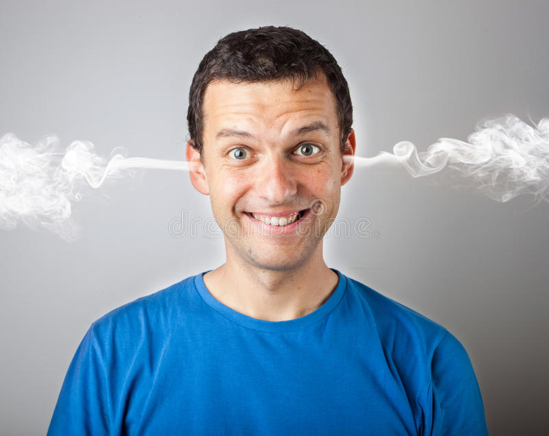 Solleciti ed irriti, uomo arrabbiato di ribaltamento con pressione capa e fumo che esce dalla sua testa immagine stock