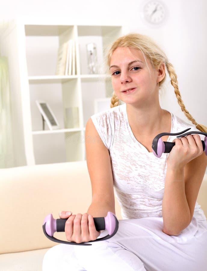 Sollevamento pesi della ragazza dell'adolescente Belle giovani donne che si esercitano con la testa di legno a casa fotografie stock libere da diritti
