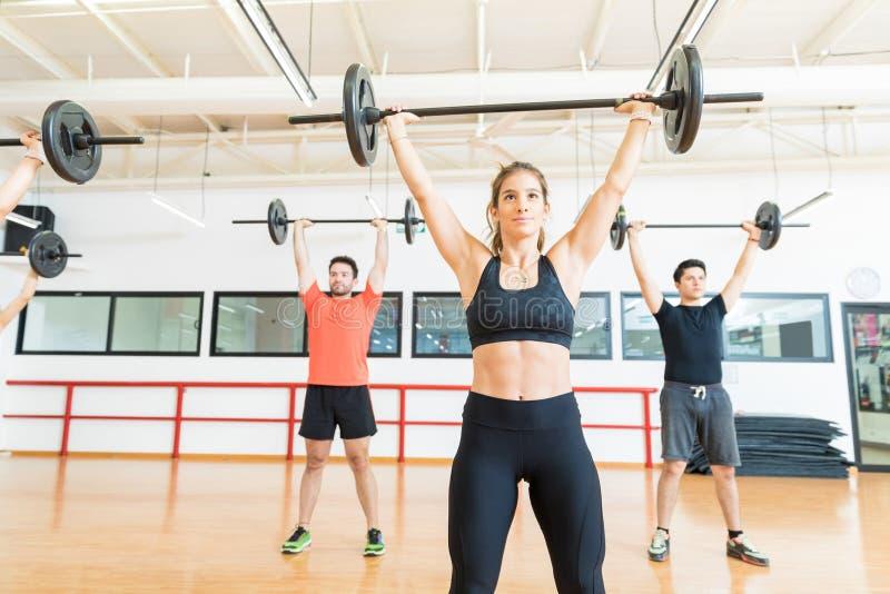 Sollevatore pesi che si esercita con il bilanciere nel club di salute immagini stock libere da diritti