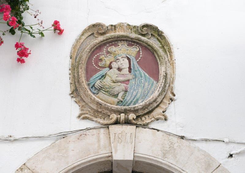 Sollievo del bambino e di Madonna sopra una porta in Locorotondo, Italia immagini stock