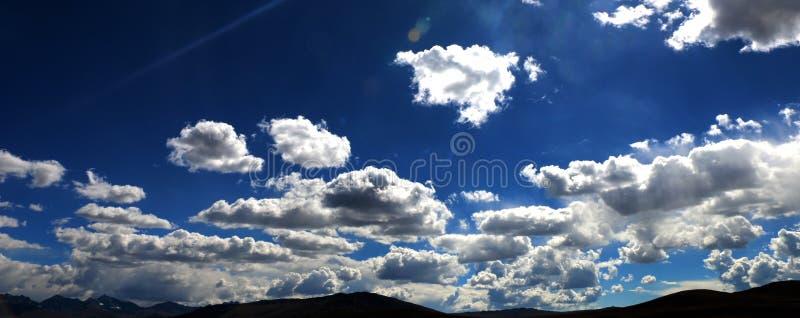 Solljus Crosing molnen och den blåa himlen arkivfoto