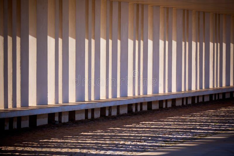 Solljus och skuggor till och med kolonner av byggnad arkivfoto