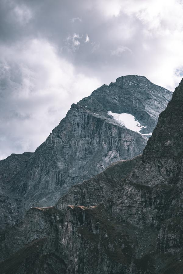 Solljus på den alpina dalen med glödande bergmaxima och sceniska moln Italienska franska fjällängar, sommarloppdestination, tonad arkivfoton