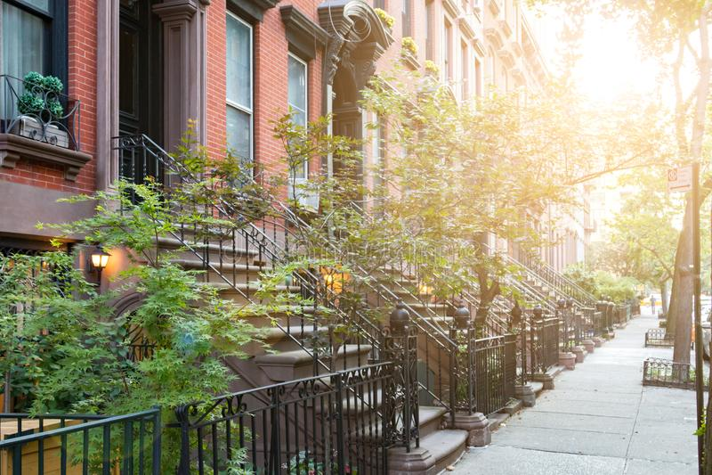Solljus skiner på historiska rödbrun sandstenbyggnader i New York City arkivfoton