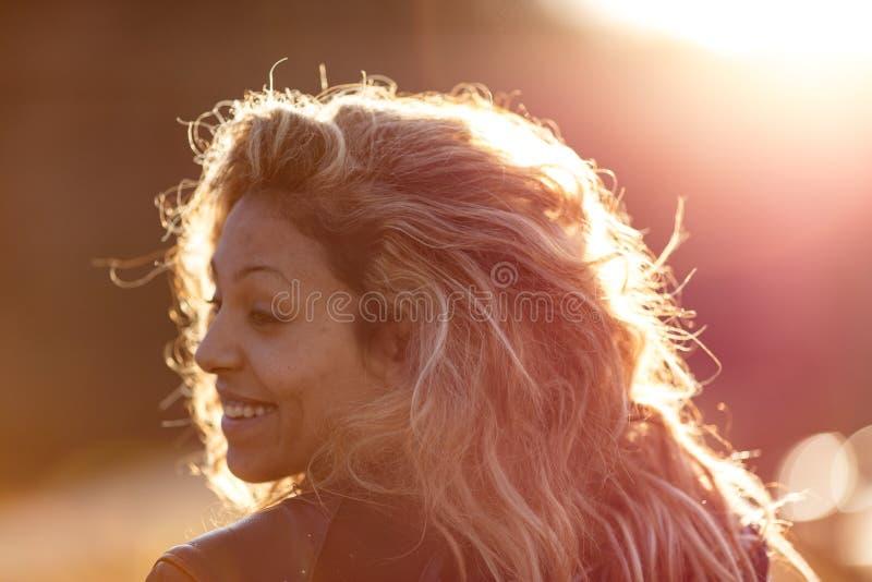 Solljus som borstar motorbikerhårkvinnan royaltyfri bild