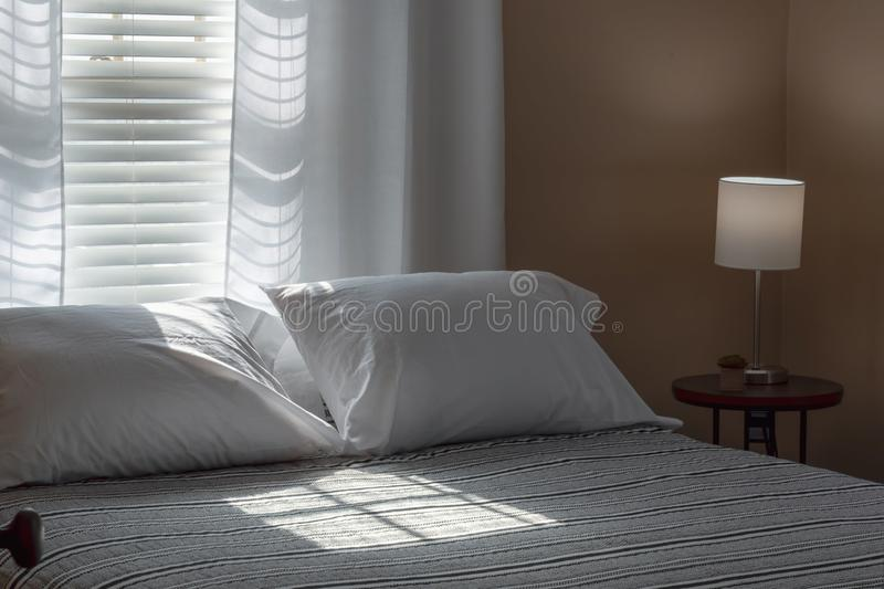 Solljus som kommer till och med rullgardiner på säng royaltyfri bild