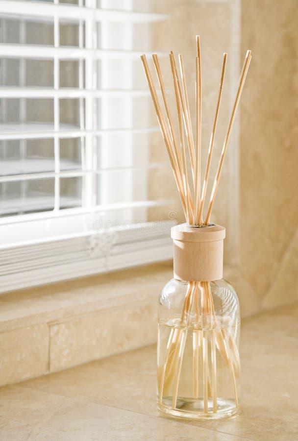 Solljus som skiner till och med fönsterrullgardiner på doftdiffusorn på räknare för stentegelplattabadrum Rent, ljust nytt hushem royaltyfri foto