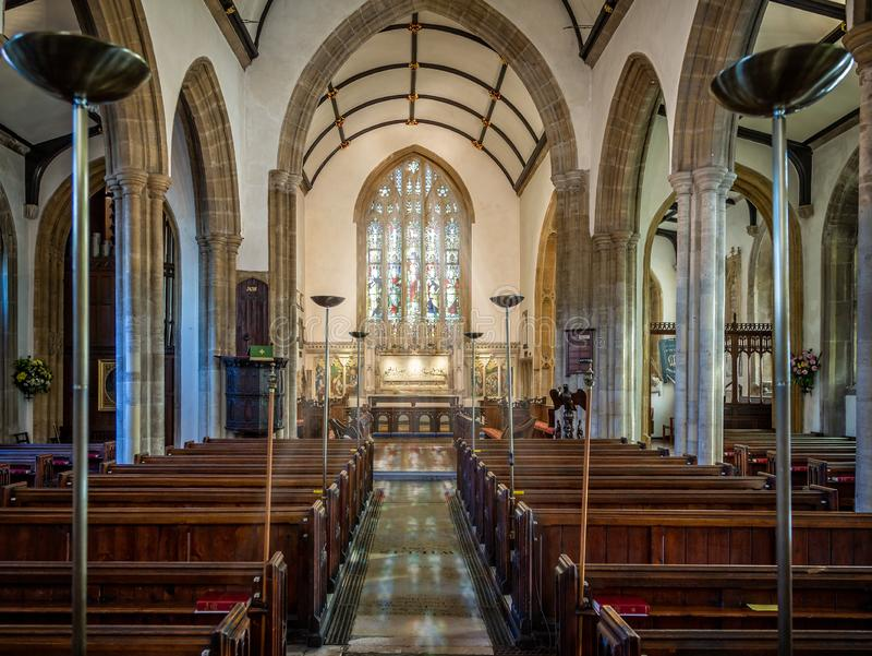 Solljus som strömmar till och med nedfläckat galssfönster med reflexion på golv i St Peters Church, Dorchester, Dorset arkivbild