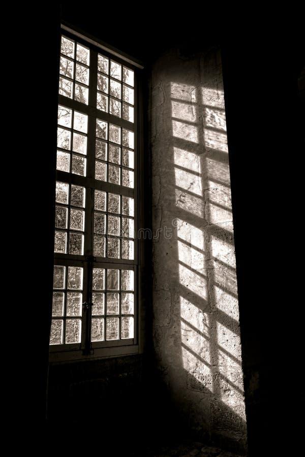 Solljus till och med ett gammalt antikt fönster med skugga arkivfoto