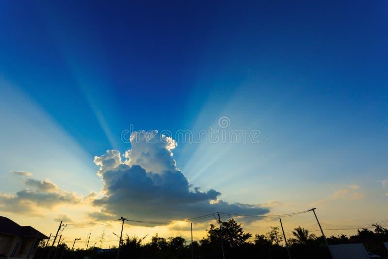Solljus till och med molnet på klar blå himmel arkivbild