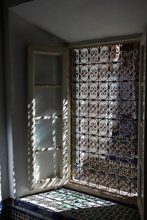 Solljus till och med utsmyckat metallfönstergaller arkivfoto
