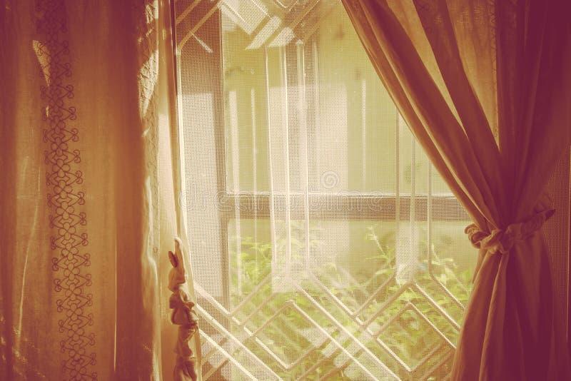 Solljus utifrån som raying till och med den bruna gardinen och träfönstret till vardagsrum royaltyfria foton